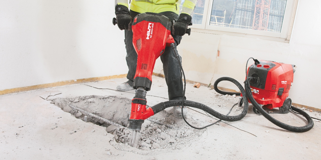 TE 2000-AVR concrete demolition hammer being used with a dust removal system and vacuum cleaner for virtually dust-free chiseling / breaking